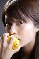 レモンをかじる20代日本人女性のビューティーイメージ