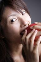 リンゴをかじる20代日本人女性のビューティーイメージ