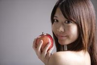 リンゴを持つ20代日本人女性のビューティーイメージ