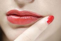 20代白人女性の赤い口紅をつけた口元と指先