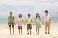 浜辺で手を繋ぐ子供達