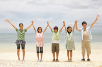 浜辺で手を繋ぎ手をあげる子供達