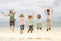 浜辺でジャンプする子供達