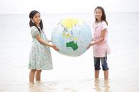 海辺で地球儀を持つ女の子達