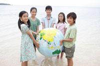 海辺で地球儀を持つ子供達