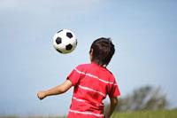 サッカーボールで遊ぶ男の子の後姿