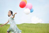 草原で風船を持ち走る女の子