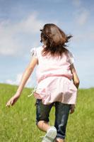 草原を走る女の子の後姿