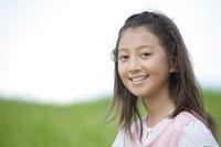草原で佇む笑顔の女の子