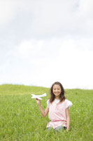 草原で飛行機を持つ女の子