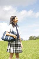 草原に立つ中学生の女の子