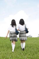 草原を歩く中学生の女の子達の後姿