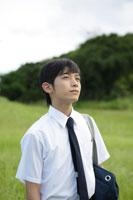 草原に立つ中学生の男の子