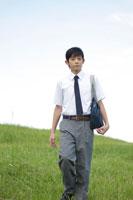 草原を歩く中学生の男の子