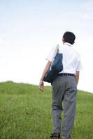 草原を歩く中学生の男の子の後姿