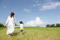 草原を走る母と娘の後ろ姿
