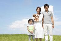 草原に立つ家族と犬