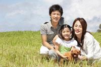 草原に腰を下ろす家族と犬