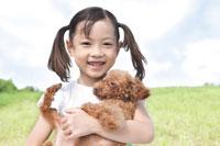 草原で犬を抱っこする少女