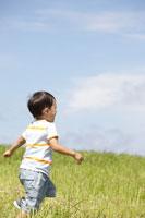 草原で走る男の子の後姿