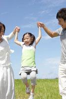 ジャンプする娘と手をとる両親
