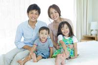 ベッドでくつろぐ家族 30018001714A| 写真素材・ストックフォト・画像・イラスト素材|アマナイメージズ