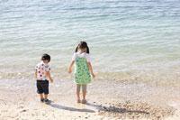 海辺の男の子と女の子の後姿