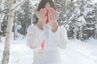 雪の中で若い女性の手から舞い散る花びら