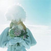 雪の中で花束を持って佇む日本人の若い女性