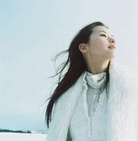雪の中で朝日に顔を向ける日本人の若い女性