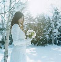 雪の中で花束を持つ日本人の若い女性 30019000091| 写真素材・ストックフォト・画像・イラスト素材|アマナイメージズ