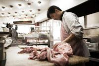 肉をさばく肉屋の店主