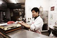 肉を計る肉屋の店主