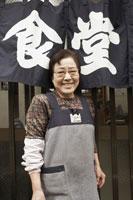 暖簾の前で微笑む定食屋の女将 30020000152| 写真素材・ストックフォト・画像・イラスト素材|アマナイメージズ
