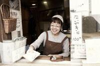 たい焼きを差し出すたい焼きやの女将 30020000158| 写真素材・ストックフォト・画像・イラスト素材|アマナイメージズ