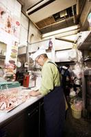 肉をさばく肉屋の店員