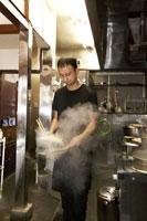 麺の湯切りをするラーメン屋の店主