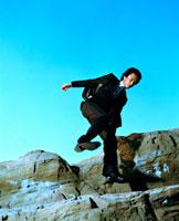 岩場を跳ぶ日本人青年ビジネスマン