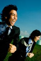 芝生を走る2人の日本人青年ビジネスマン