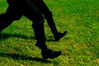 芝生を走る2人の日本人青年ビジネスマンの足元