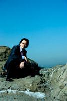 岩場に座る日本人青年ビジネスマン