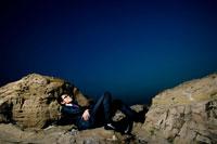 岩場で煙草を吸う日本人青年ビジネスマン