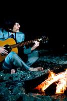 焚火のそばでギターを弾く日本人青年ビジネスマン