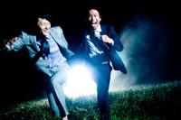 草むらを走る2人の日本人青年ビジネスマン