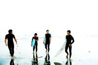 ボードを持ち海から上がる男女