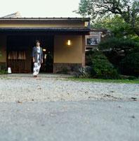 旅館の前に立つ浴衣姿の20代日本人女性