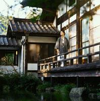 旅館の縁側に立つ浴衣姿の20代日本人女性