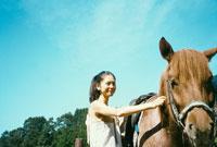 馬をなでる20代日本人女性