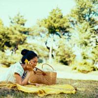 公園で携帯電話で話す20代日本人女性