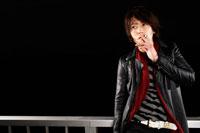暗闇でタバコを吸う20代の日本人男性